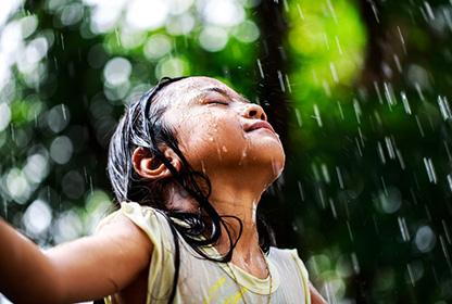 kleines Mädchen im Sommerregen Wasserreise